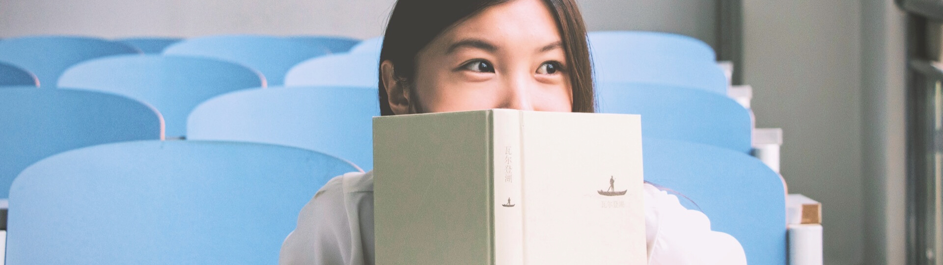 Woman peering over the top of book