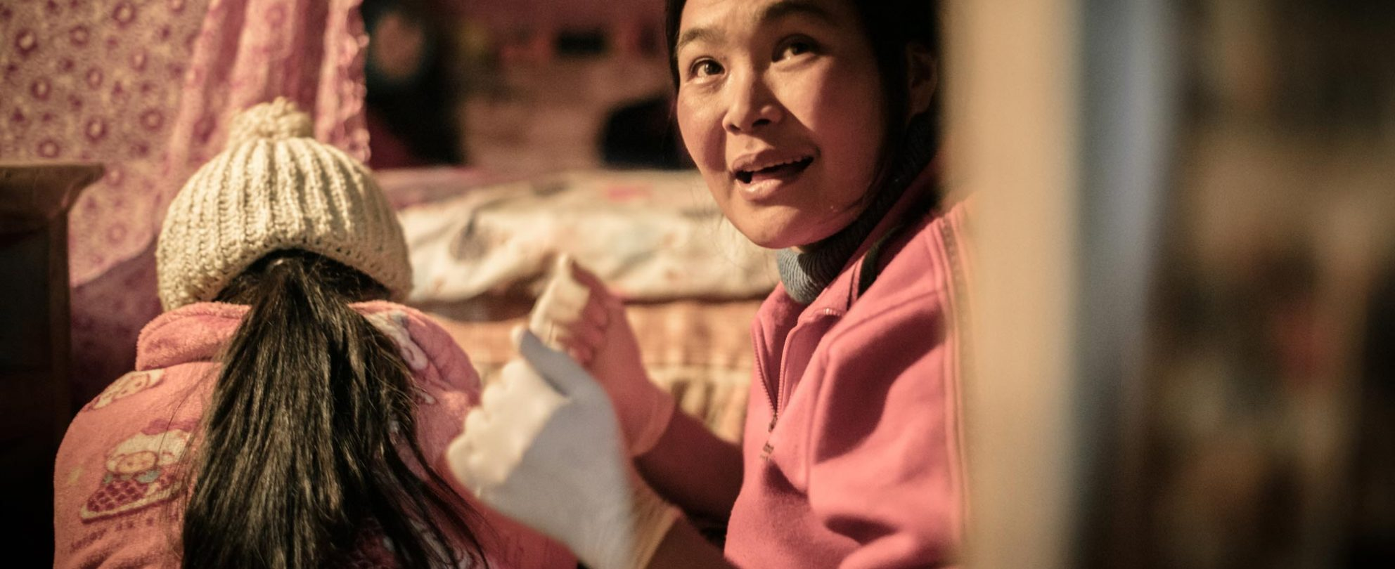 An HPA health worker with rubber gloves on helping another woman