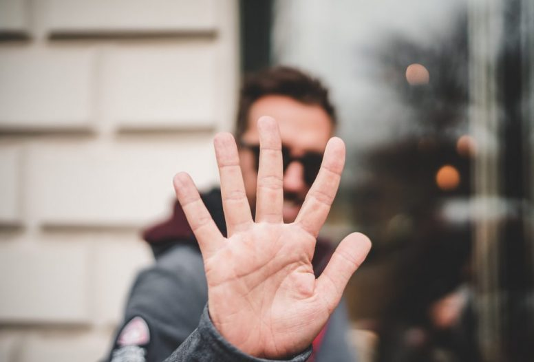 Man putting palm of hand up to camera