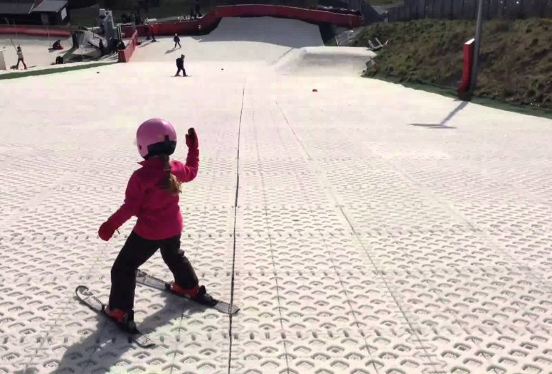 Little girl skiing down a dry ski slope