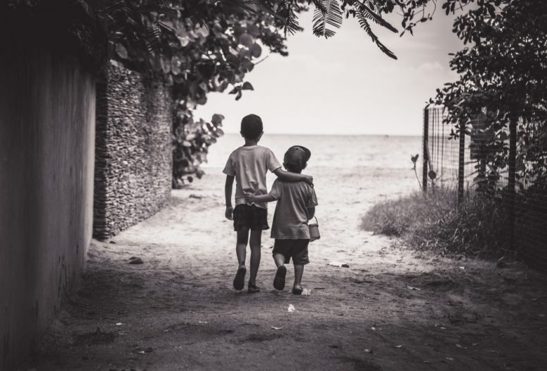 Two young boys wearing caps walking with arms around each other