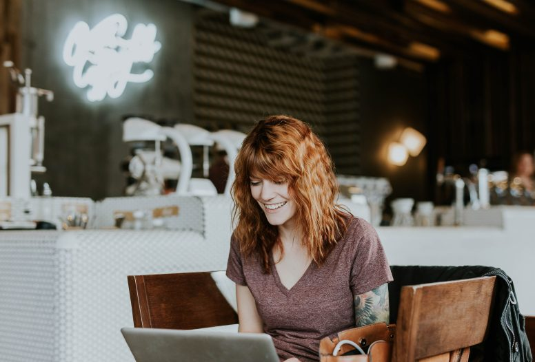 tattooed woman smiling at her laptop