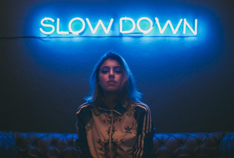 Woman standing in front of neon light that reads slow down