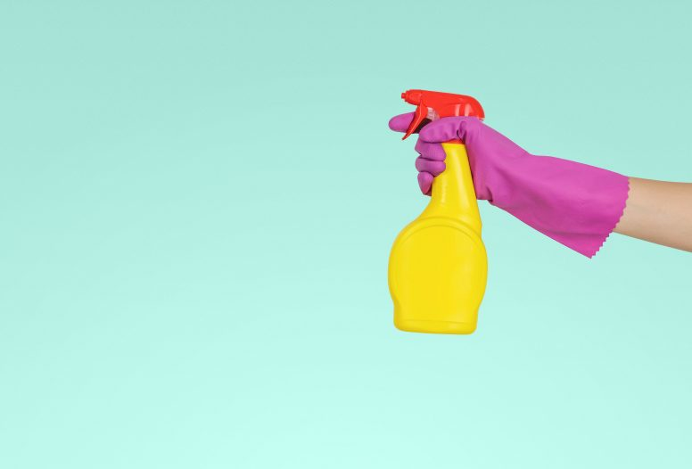 Hand in rubber glove holding spray bottle of cleaning liquid