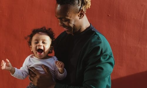 Laughing man holding a laughing baby