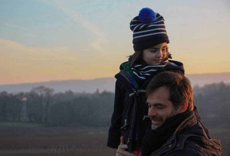 Man with child wearing winter clothes in the countryside