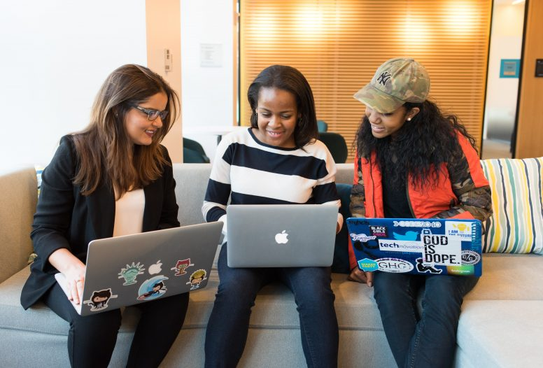Three women sitting on a sofa looking at their laptops