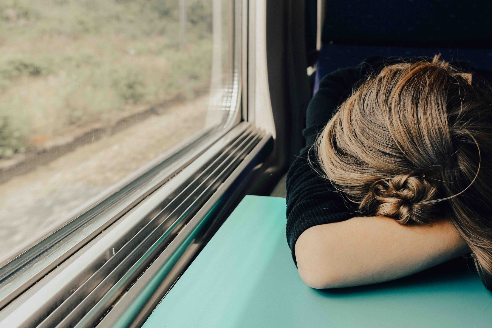 Woman with her head on the table asleep on a train