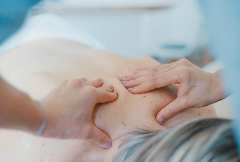 Hands massaging a persons back