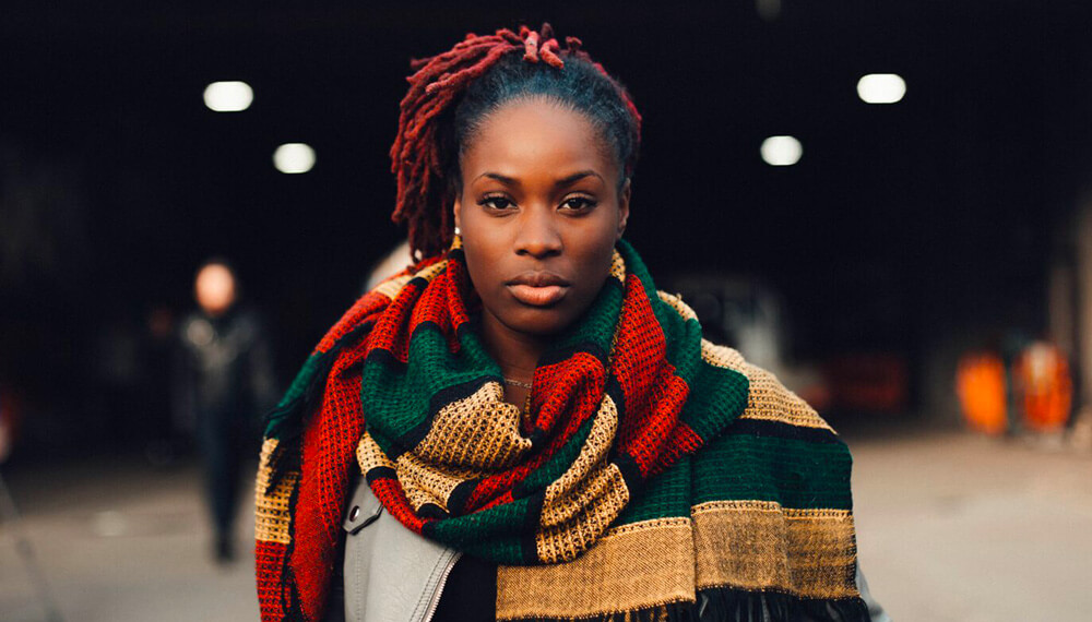 Black woman looking at camera with large scarf