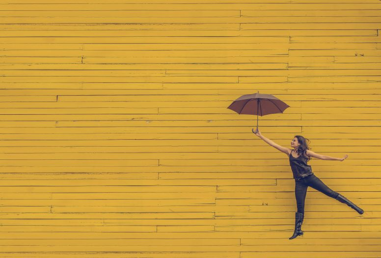 Woman flying up using an umbrella