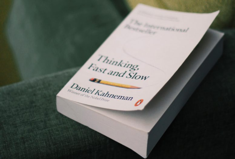 The cover to Daniel Kahneman's 'Thinking Fast and Slow' on the arm of a sofa