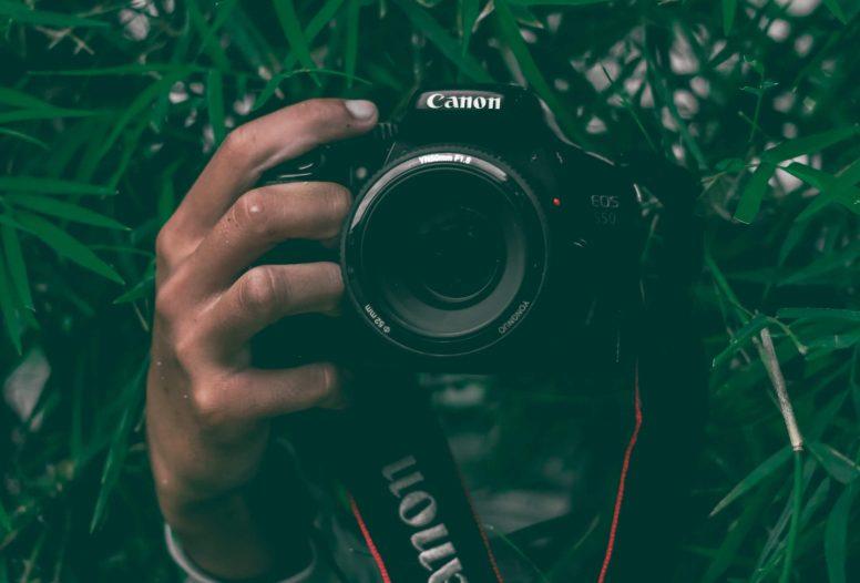 A man's hand holding a DSLR camera