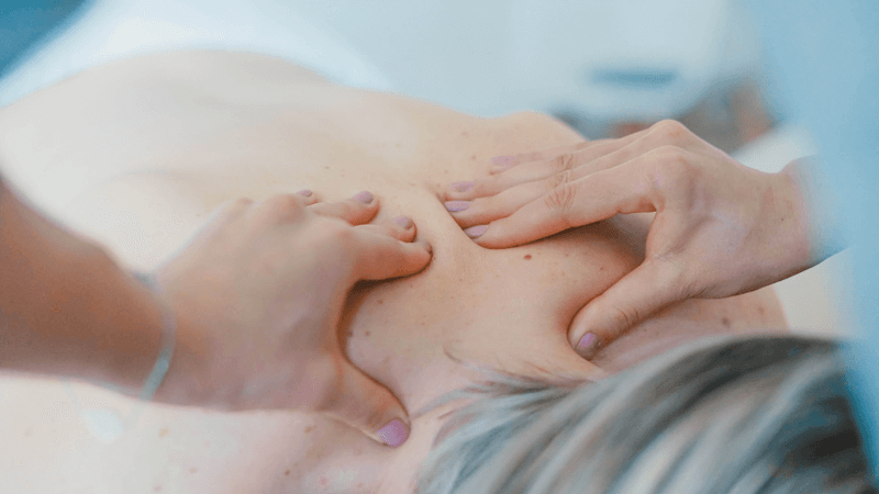 Close up of a woman massaging a client's back