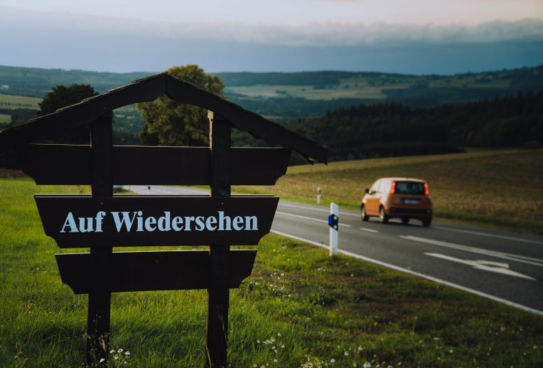 Car driving past a sign saying auf wiedersehn