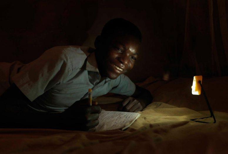 A man works a night by a SolarAid light